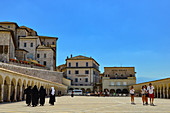 Nuns and tourists meet in the courtyard of the Basilica of San Francesco, Assisi, Italy