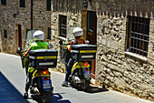 Two postmen on their scooters in the old town of Assisi, Italy