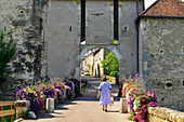 An old woman walks through the city gate decorated with colorful flowers, Liverdun, France