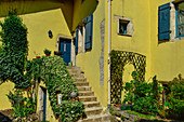Lush garden at a yellow house with blue shutters in Liverdun on the Moselle, France