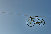 A bicycle hangs on a rope high above a street near Le Puy, France