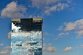 High-rise building with glass facade reflecting dark clouds and intense light, Barcelona, Catalonia, Spain