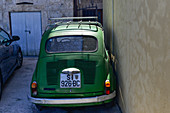 Parked Fiat 500 directly on a house wall, Sibenik, Adriatic Sea, Dalmatia, Croatia