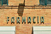 Old lettering Farmacia at a pharmacy, Maiolati Spontini, Italy