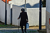 An old woman comes from shopping and walks through the village street, Odeceixe, Algarve, Portugal