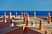 Red roofs with chimneys in front of the blue Atlantic, Luz, Algarve, Portugal