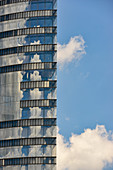 Reflective barrel of an office building with clouds and sky, Vienna, Austria