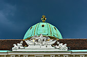 Gold ornate dome and ornaments on the roof of an old building in Vienna, Austria