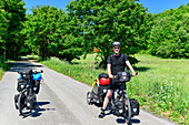 Cyclists on a long tour with full luggage and trailers on a lonely road near Breitenbrunn, Austria