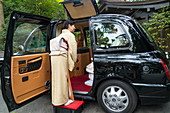 Woman in traditional dress escorting couple into a chauffeur-driven car in Tokyo, Japan