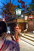 Women dressed in traditional geisha dress being photographed on mobile phone, Kyoto, Japan