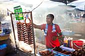 Grilling chicken wings in night market, Kota Kinabalu, Malaysia