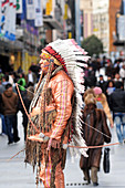 MADRID - MARCH 01 2010:Native American Indian living statue standing  against Spanish pedestrians at Puerta del Sol street, one of the the most busiest places in Madrid.