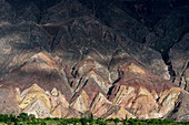 Colorful rock formations and erosion on a hillside in the Andes Mountains near Purmamarca, Jujuy Province, Argentina.