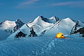 Illuminated tent surrounded by Monte Rosa glaciers, Gobba di Rollin, Monte Rosa, Aosta Valley, Italy