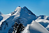 Mountaineers climbing Breithorn Centrale from Breithorn Occidentale, Lyskamm on background, Aosta Valley, Italy, Europe