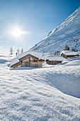 landscape of snow-covered mountain huts in the locality Ciamp de Lobia, Fedaia pass, Rocca Pietore, Marmolada, Dolomites, Belluno, Veneto, Italy