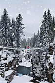 two young hikers on the suspension bridge over the gorge of the Travignolo river in a winter landscape, Paneveggio, Dolomites, Predazzo, Trentino, Italy
