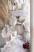 Typical mask of Carnival of Venice under the arches of the Doge's Palace, Venice, Veneto, Italy