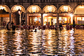People walking and swimming in the high tide in St. Mark's square, Venice, Veneto, Italy