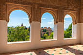 Gardens of Generalife seen from interior room of palace with arabic archways and decorated tiled floor, La Alhambra complex, Granada, Andalusia, Spain