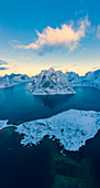 Aerial panoramic of snowy mountains and fjord at dawn, Reine, Nordland, Lofoten Islands, Norway