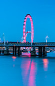 Illuminated London Eye reflected in river Thames at dusk, London, United Kingdom