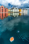 Jellyfish in Brosundet canal surrounded by Art Nouveau styled houses, Alesund, More og Romsdal county, Norway