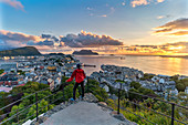 Rear view of man admiring sunset over the ocean and Alesund from Strykejernet viewpoint, More og Romsdal county, Norway