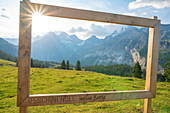 Wood signage on green meadow framing the Swiss Alps at Oeschinensee, Bernese Oberland, Kandersteg, Canton of Bern, Switzerland