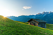 Sunburst over the green meadows of Tombal Alp, Soglio, Val Bregaglia, canton of Graubunden, Switzerland