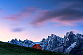 Tent in front of Piz Badile, Piz Cengalo and Sciore group lit by dawn, Tombal, Soglio, Val Bregaglia, canton of Graubunden, Switzerland