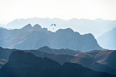 Paragliding at sunset over Val di Fassa in autumn seen from Sass Pordoi, Dolomites, Trentino, Italy