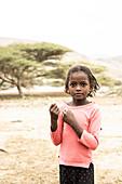 Young baby girl in the arid landscape, Melabday, Asso Bhole, Danakil Depression, Afar Region, Ethiopia, Africa