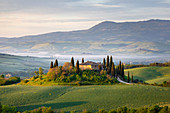 A farmhouse in the  morning between Val d'Orcia Hills. San Quirico d'Orcia, Val d'Orcia, Siena Province, Tuscany, Italy.