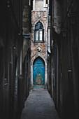 A small blue door in a very small street in Venice, Veneto, Italy.