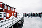 Waterfront red houses covered with fresh snow in Svolvaer. Lofoten Islands, Nordland, Norway.