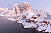 The snowy peaks and frozen sea frame the typical fisherman houses called Rorbu, Hamnøy, Lofoten Islands, Northern Norway, Europe