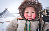 A young nenets boy dressed with the traditional coat. Daily life at the nomadic reindeer herders camp. Polar Urals, Yamalo-Nenets autonomous okrug, Siberia, Russia