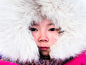 Nenets girl with the traditional fur coat at the nomadic reindeer herders camp. Polar Urals, Yamalo-Nenets autonomous okrug, Siberia, Russia