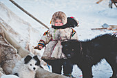 A small boy with dogs at the nomadic reindeer herders camp. Polar Urals, Yamalo-Nenets autonomous okrug, Siberia, Russia