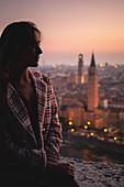 A girl looking at Verona city during sunset. Verona, Veneto, Italy