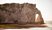 Etretat, Normandie, Frankreich. Die Klippen über dem Atlantik an einem sonnigen Tag mit dem Strand im Vordergrund.