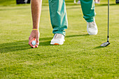 Man placing golf ball on green on golf course