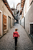 Rear view of boy walking down a narrow lane in Bormio, Lombardy, Italy.