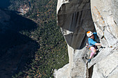 High angle view of mountaineer climbing up sheer wall of The Nose, El Capitan, Yosemite National Park.