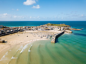 Aerial View of St Ives, a wide sandy beach and sheltered harbour with boats beach on sand at low tide.