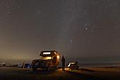 Person standing next to camper-van parked near Jordan River, British Columbia, Canada at night.