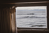 View of ocean through camper van window, surfer in the distance.