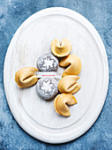 Oval dish of Fortune Cookies and small cakes.